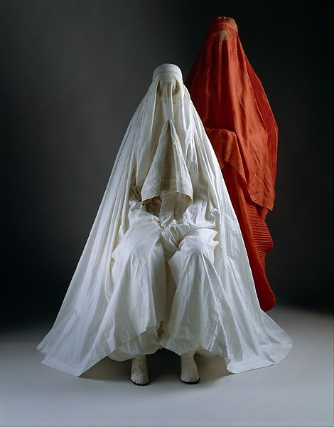 Two women wearing chadris, shrouds which cover the body from head to foot. One woman is standing and wearing red and one woman is sitting and wearing white.